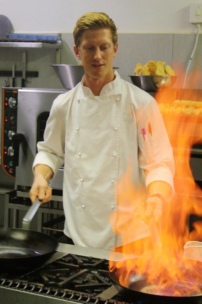 Chef Jarred Pullin creating flames at Rhino Ridge Safari Lodge